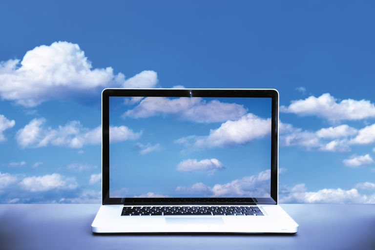 An image of a laptop computer in the clouds