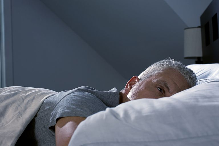 Gray-haired man lays awake in bed.