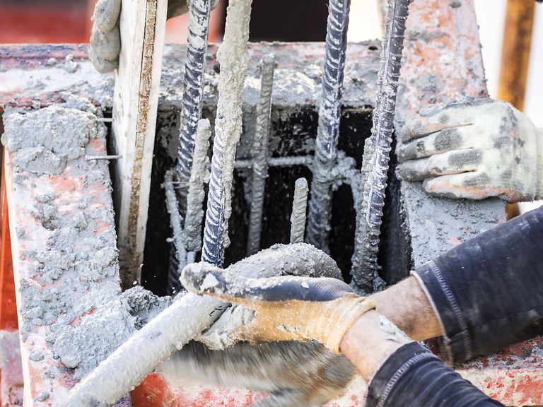 High angle view of a construction worker working at a construction site, with a hose at the hands being work with the concrete, Spain