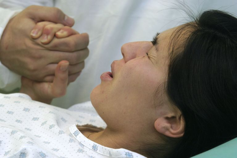 pregnant woman in labor holding man's hand