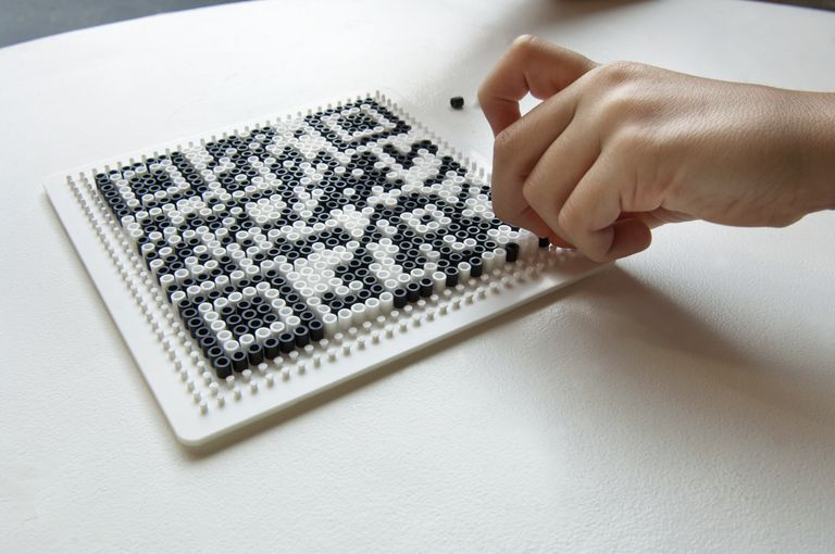 child creating a QR code with iron beads