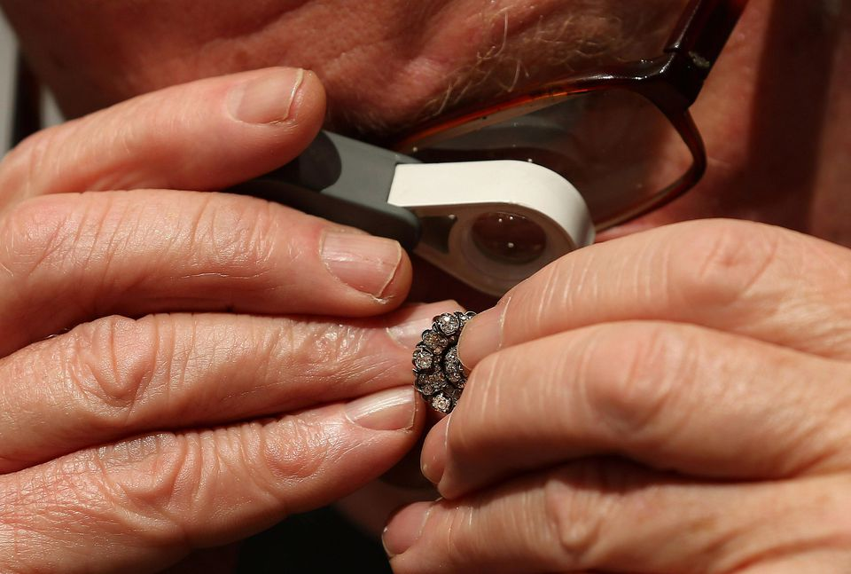 A specialist inspects a pair of antique Russian earrings ahead of the Olympia 'International Fine Art and Antiques Fair' at Olympia Exhibition Centre on June 5, 2013 in London, England.