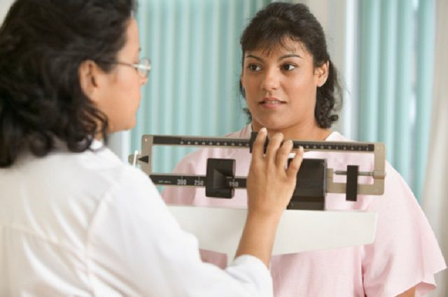 Doctor weighing female patient on scale