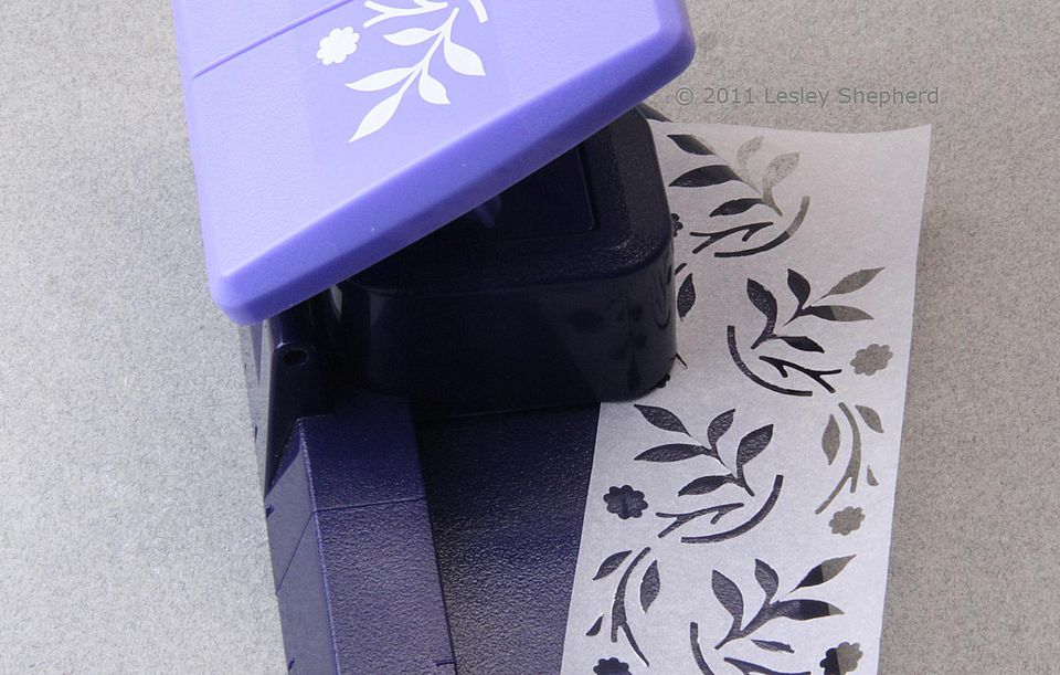 Repeating stencil of leaves and flowers in dollhouse scale punched into baking parchment paper.