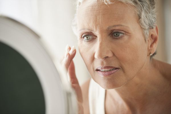 mature woman looking at face in mirror