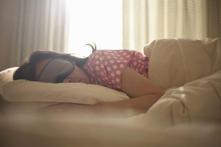 Woman in eye mask asleep in bed