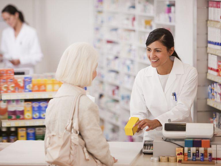 Pharmacy technician handing medication to customer in drug store