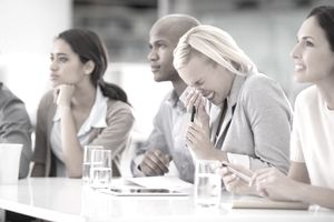 Shot of a businesswoman sneezing during a meeting with her colleagues