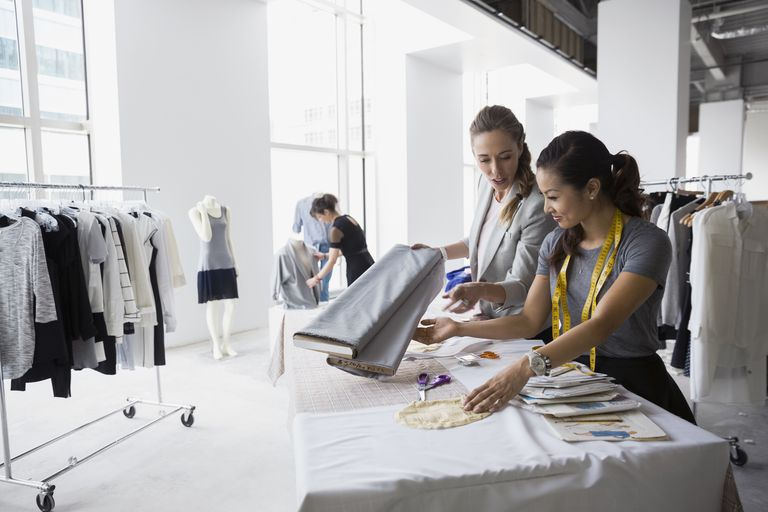 Fashion designers working with fabric and sewing patterns