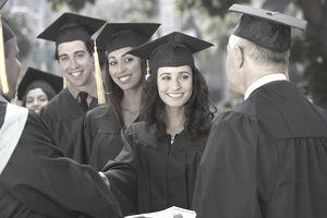 Graduate students receiving diplomas at graduation ceremony