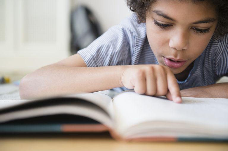 Mixed race boy reading book at desk