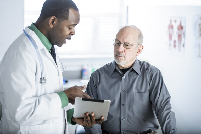 Older male patient talking with doctor over tablet