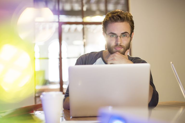 Focused casual businessman working at laptop in office
