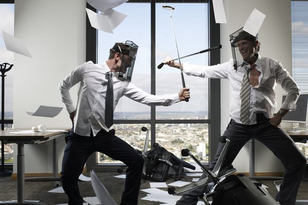 Businessmen fighting with golf clubs