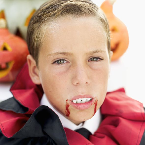 This young vampire is using fake blood as part of his costume.