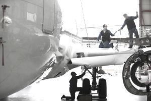 Engineers repairing wing and landing gear on passenger jet in hangar