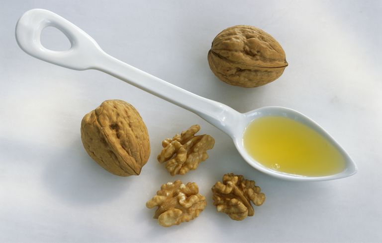 Spoonful of walnut oil and walnuts, studio shot