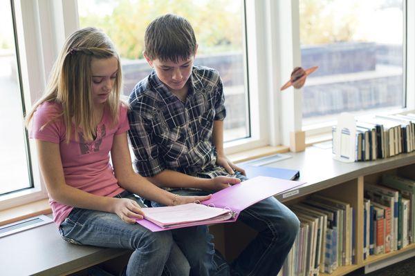 Teen girl and boy working on homework together