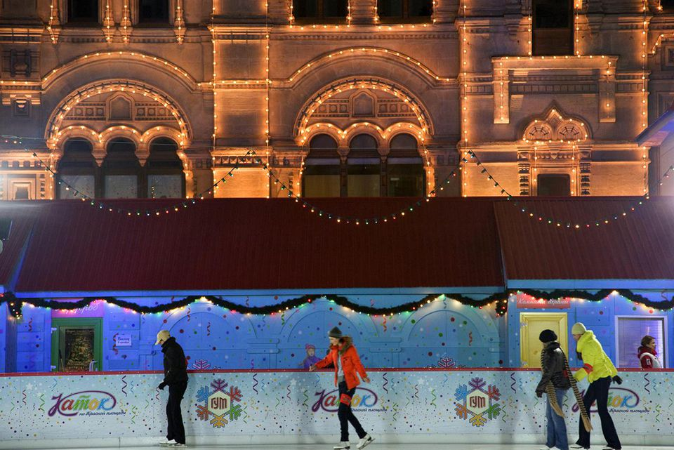 Russia, Moscow; Youths ice-skating in front of the huge Shopping Mall, the Gum, on Red Square in winter