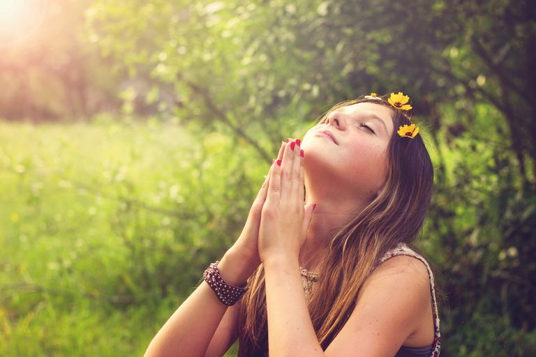 Teenage Girl Praying Against Trees In Forest