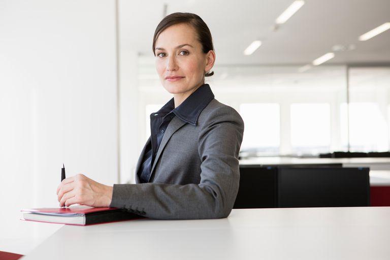 Businesswoman at desk holding pen