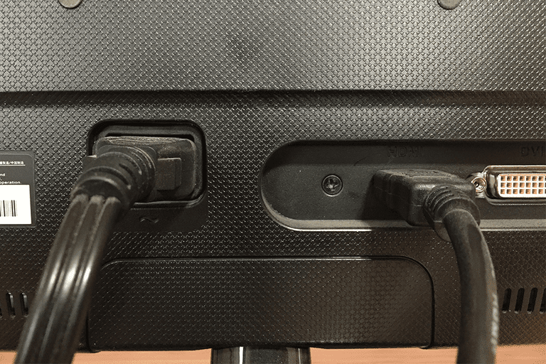 Picture of a power cable and HDMI cable plugged into the back of a monitor