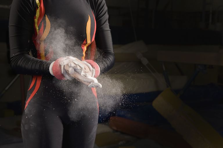 Hispanic female gymnast chalking hands