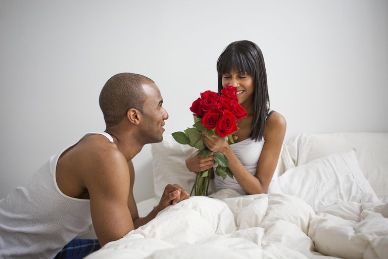 Man Giving Woman a Bouquet of Red Roses in Bed