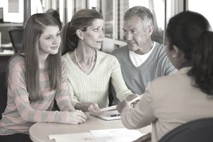 Parents and their child talking to a financial adviser
