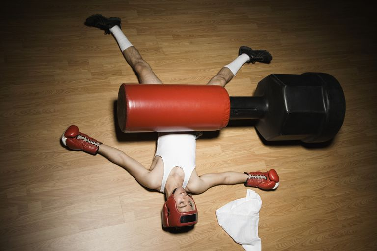 man laying under boxing practice dummy