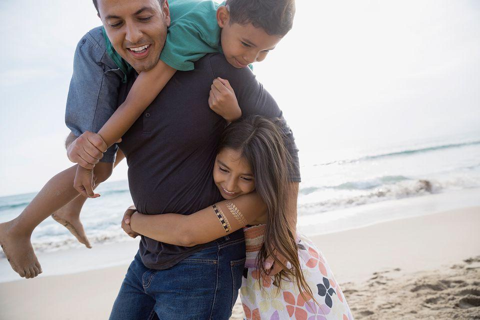 Playful family on sunny beach