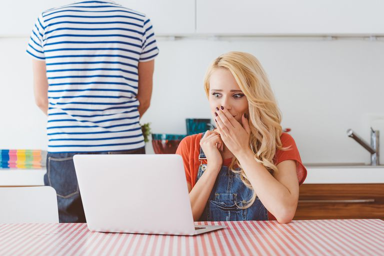 Worried woman using a laptop in the kitchen