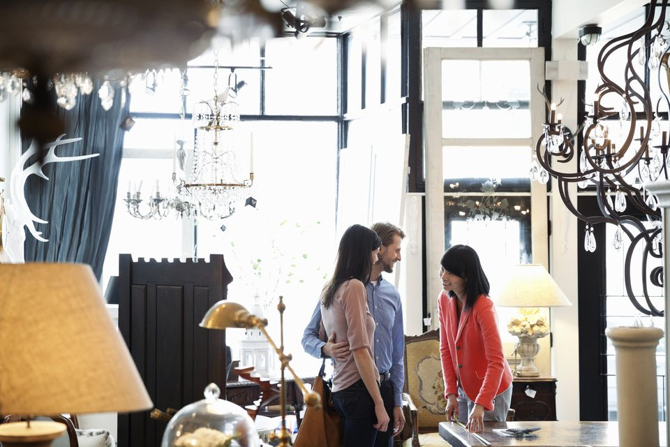 Female business owner helping customers in furniture store