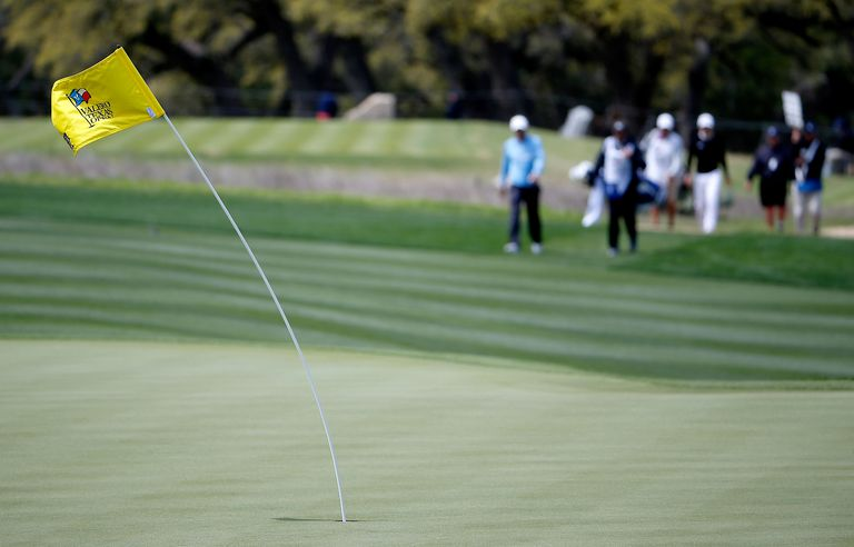 Golf flagstick bends over in a strong wind