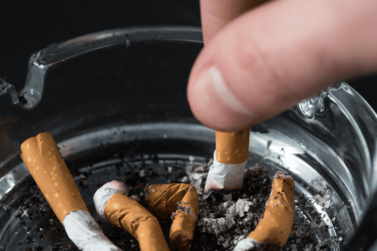 Man stubbing out a cigarette in an ash tray