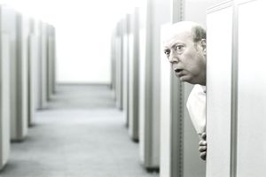 older man peering around a cubicle