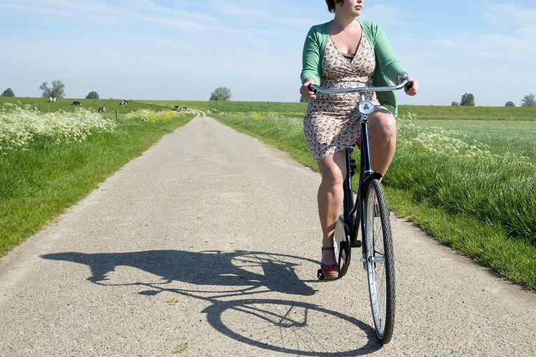 Woman riding bicycle on rural road
