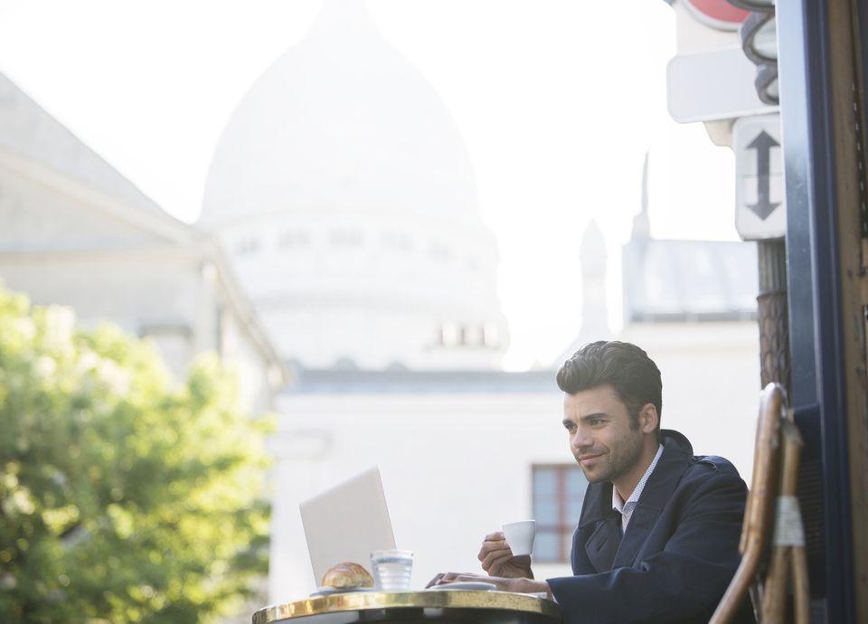 Man using laptop at Paris cafe
