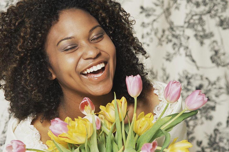 Smiling woman holding a bunch of tulips.