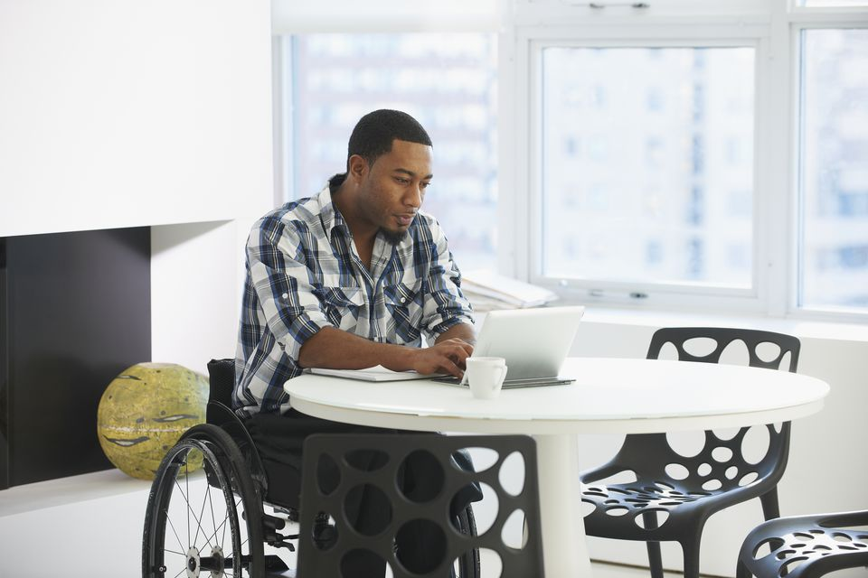 Black businessman in wheelchair using laptop at table