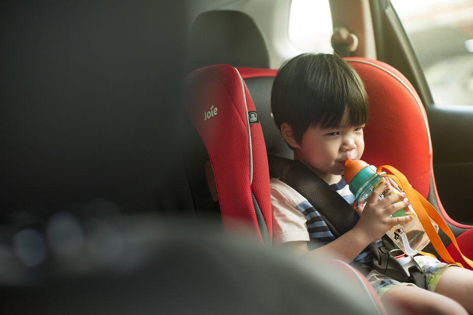 Asian toddler boy drinking in car.