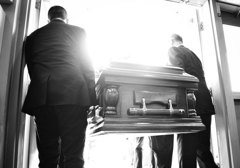 Two pallbearers carrying a casket