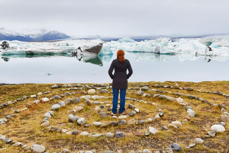 Tourist in stone circle looks out on Jokulsarlon