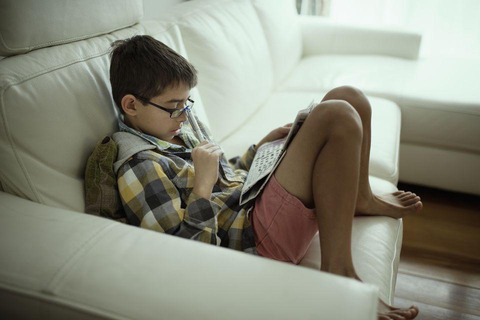 Boy solving crossword puzzles