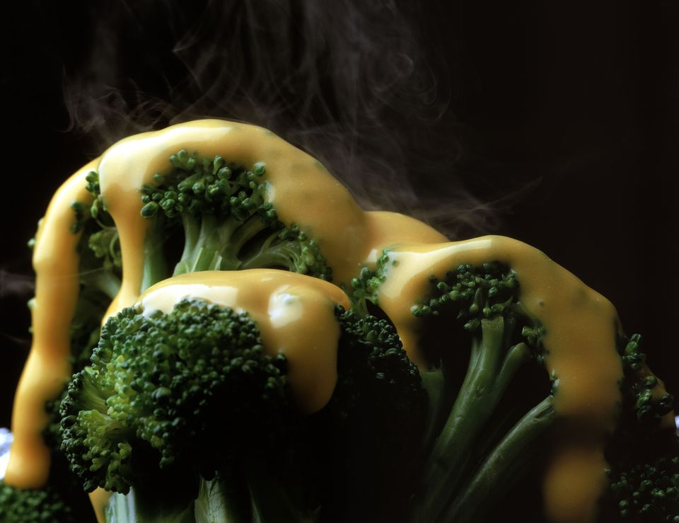 Steam rising from broccoli with melted cheese sauce