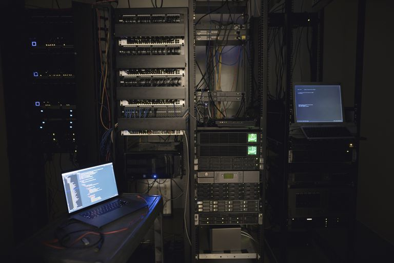 Laptop and server panels in dark server room
