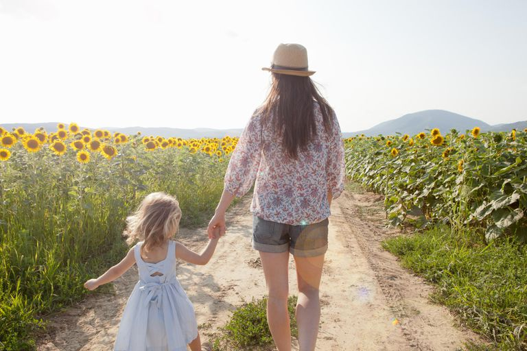 Mother and daughter walking through field of sunflowers