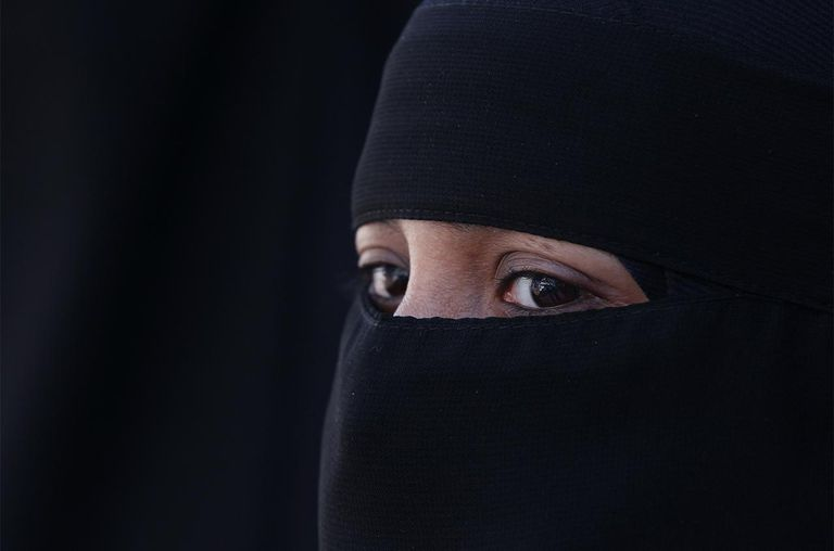 A woman wears an Islamic niqab veil stands outside the French Embassy during a demonstration on April 11, 2011 in London, England