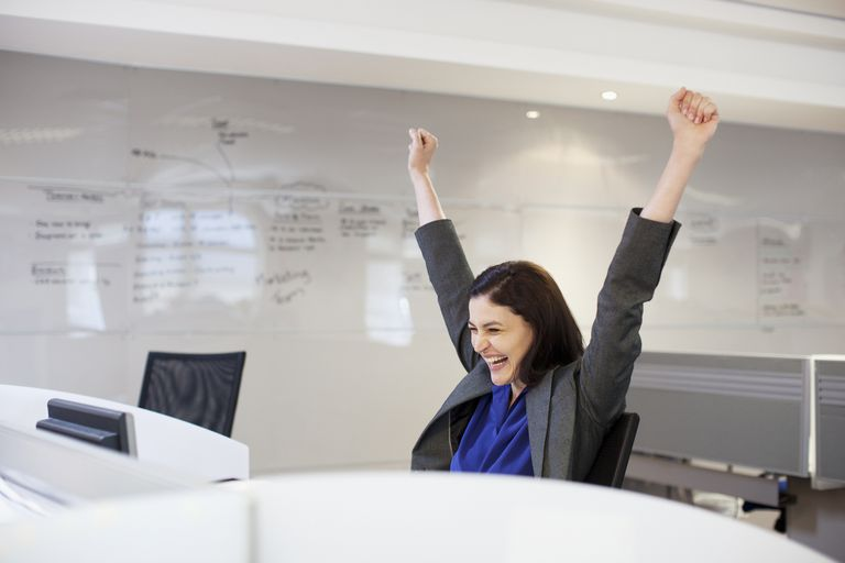 triumphant businesswoman with hands in the air