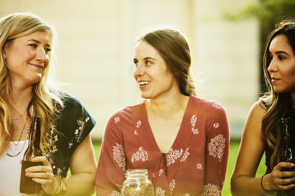 Smiling women sharing drinks in backyard on summer evening